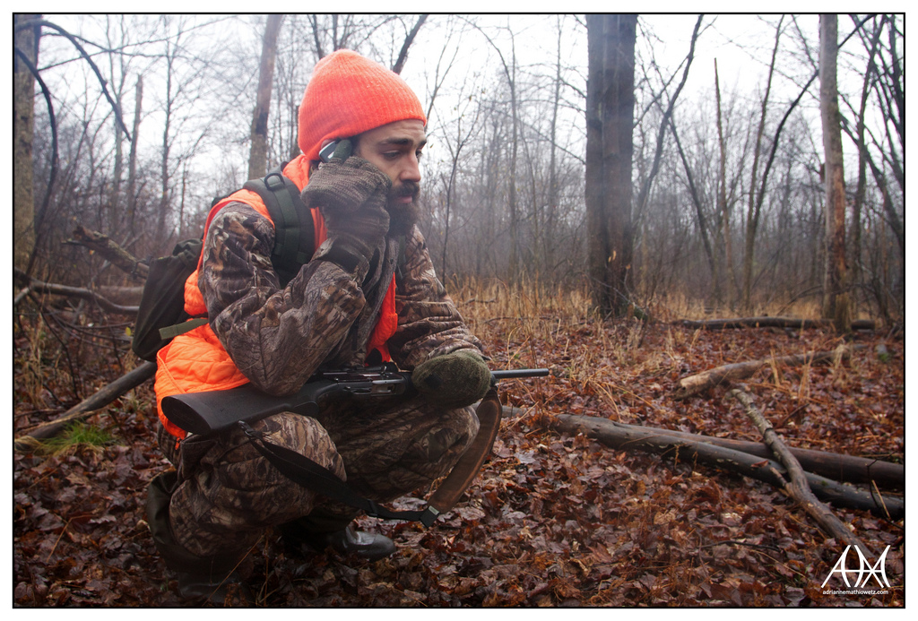 Hunter crouches in the woods with his rifle and cell phone